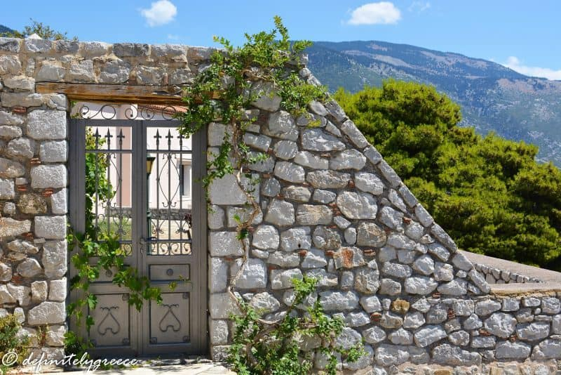 slanted stone wall with delicate door looking out over a hill in osios loukas monastery area - welcome to central Greece