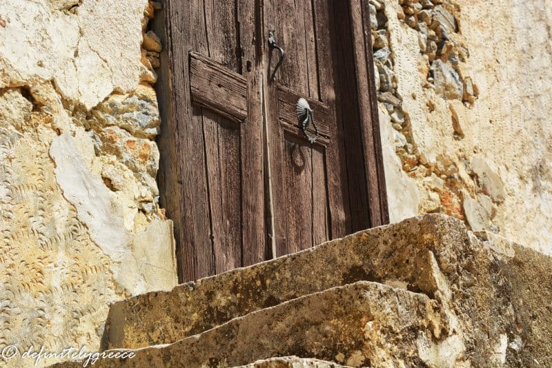 old wooden brown door - on steps leading up to a house - welcome to central Greece