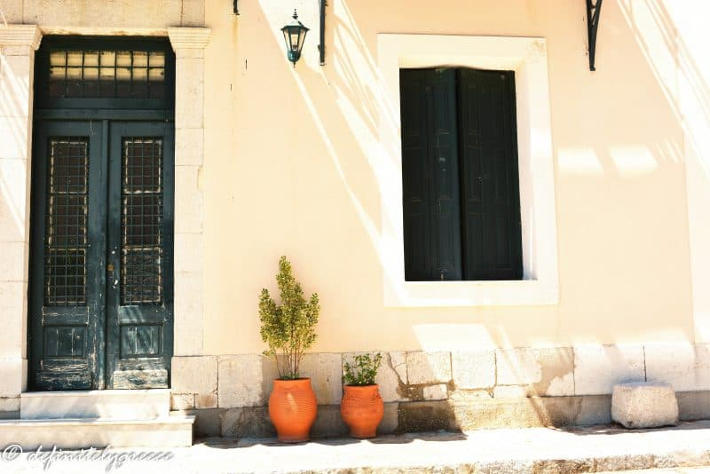 front windows and door with two terracota plants - sun shining through - welcome to central greece