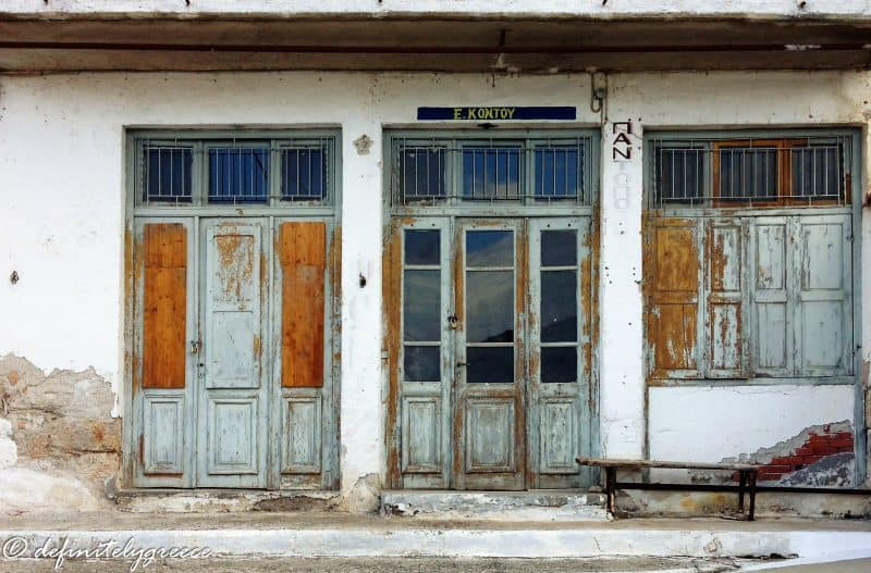 store front of abandoned shop in greece - pastel colour - rust - welcome to central greece