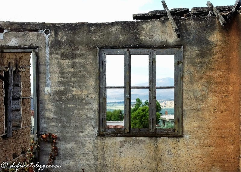 inside of abandoned house with window framing view of surrounding valleys - welcome to central Greece