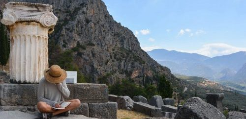 women travel groups Greece - woman with hat reading in delphi