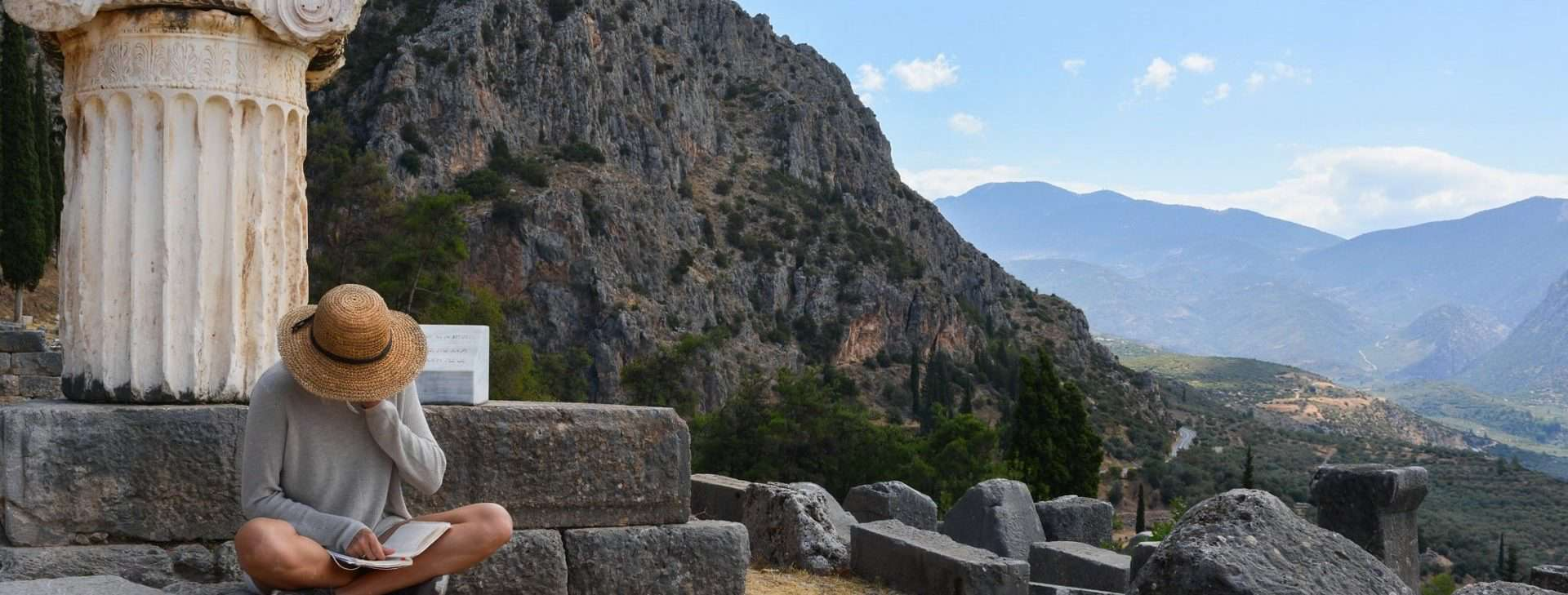 Efi reading in Delphi among the ruins - Our Story Definitely Greece