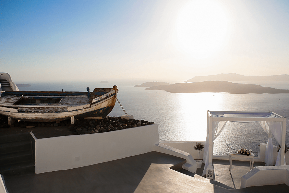 get married in santorini - boat with wedding altar on the left and santorini view