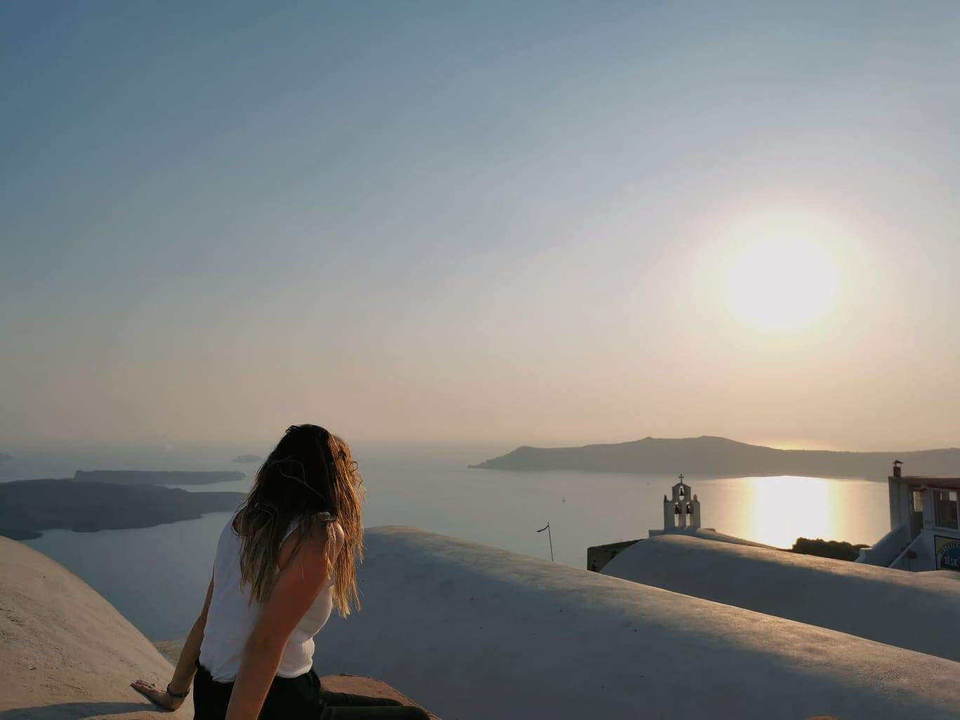 sunset over Santorini with Girl looking out at view over Caldera - Greek Holiday Destinations